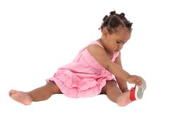 Beautiful african baby girl putting on an slipper Royalty Free Stock Images