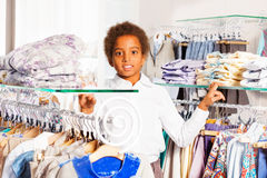 Beautiful African boy stands between clothes rows Royalty Free Stock Photography