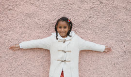 Beautiful african child with a brick a pink wall Royalty Free Stock Image