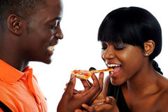 Beautiful african couple eating pizza. Isolated over white, closeup shot Stock Image