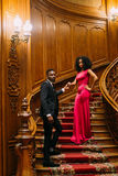 Beautiful african couple posing on the vintage stairs. Luxurious theatre interior background Stock Photos