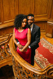 Beautiful african couple posing on the vintage stairs. Luxurious theatre interior background Royalty Free Stock Photo