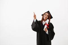 Beautiful african female graduate smiling pointing finger in side over white background. Stock Images