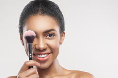 Beautiful african girl applying blush on skin royalty free stock images