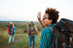 Beautiful african girl with backpack smiling, greeting, friends travelers background. Stock Photos