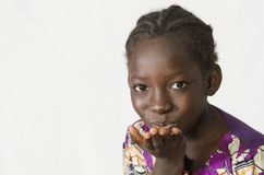 Beautiful African girl blowing a kiss, isolated on white. Beautiful shot of African children taken in a studio in Bamako, Mali Royalty Free Stock Photography