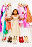 Beautiful African girl choosing clothes in shop. Beautiful African girl choosing clothes while standing between hangers with colorful bright dresses, clothes and stock image