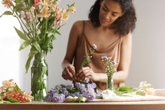 Beautiful african girl florist smiling making bouquet in flower shop over white wall. Stock Photos