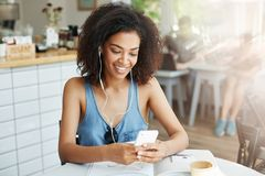 Beautiful african girl in headphones smiling looking at phone screen sitting resting in cafe. Copy space Royalty Free Stock Photography