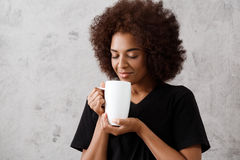 Beautiful african girl holding cup, eyes closed, over light background. Young beautiful african girl holding cup, smiling, eyes closed, over light background Stock Photos