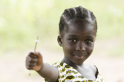 Beautiful African girl holding a pen outdoors. Young girl holding pen in hand and looking at camera on blurred background Stock Images