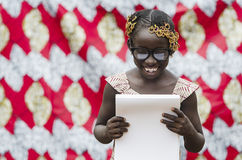 Beautiful African Girl Reading Outdoors. Young african girl with traditional accessories in hair reading papers Royalty Free Stock Photo