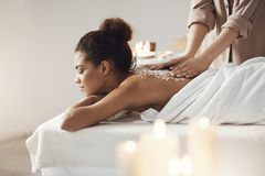 Beautiful african girl resting enjoying spa health massage with sea salt. Young beautiful african girl resting enjoying spa health massage with sea salt Stock Images