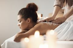 Beautiful african girl resting enjoying spa health massage with sea salt. Young beautiful african girl resting enjoying spa health massage with sea salt Stock Photography