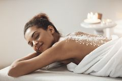 Beautiful african girl resting relaxing with sea salt on back in spa salon. Closed eyes Royalty Free Stock Photos