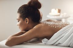 Beautiful african girl resting relaxing with sea salt on back in spa salon. Closed eyes Royalty Free Stock Photography