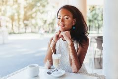 Beautiful african girl with skin problems and sits in a cafe for. A cup of hot tea Vitiligo Royalty Free Stock Images