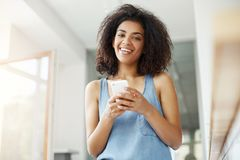 Beautiful african girl smiling looking at camera holding phone sitting in cafe. Copy space Stock Images
