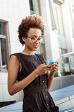 Beautiful african girl smiling looking at phone walking down city. Young beautiful african girl in glasses smiling looking at phone walking down city. Fashion Stock Photography