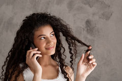 Beautiful african girl smiling, speaking on phone over beige background. Royalty Free Stock Photos