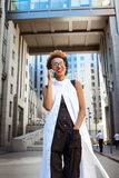 Beautiful african girl smiling speaking on phone walking down city. Young beautiful african girl in glasses smiling speaking on phone walking down city. Fashion Stock Images