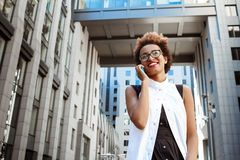Beautiful african girl smiling speaking on phone walking down city. Young beautiful african girl in glasses smiling speaking on phone walking down city. Fashion Stock Photos