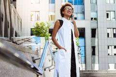 Beautiful african girl smiling speaking on phone walking down city. Young beautiful african girl in glasses smiling speaking on phone walking down city. Fashion Royalty Free Stock Image