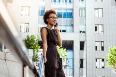 Beautiful african girl smiling speaking on phone walking down city. Young beautiful african girl in glasses smiling speaking on phone walking down city. Fashion Royalty Free Stock Photo