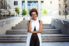 Beautiful african girl smiling speaking on phone walking down city. Young beautiful african girl in glasses smiling speaking on phone walking down city. Fashion Royalty Free Stock Photography