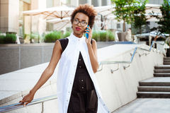 Beautiful african girl smiling speaking on phone walking down city. Young beautiful african girl in glasses smiling speaking on phone walking down city. Fashion Stock Image