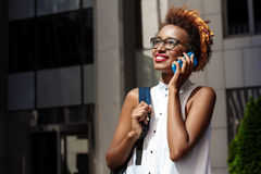 Beautiful african girl smiling talking on phone walking down city. Young beautiful african girl in glasses smiling talking on phone walking down city. Fashion Royalty Free Stock Photography