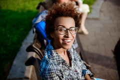 Beautiful african girl smiling, winking, sitting on bench in park. Stock Photography
