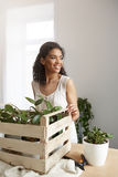 Beautiful african girl smiling working with plants in box at workplace. White wall. Royalty Free Stock Image