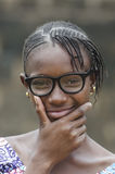 Beautiful African girl thinking outdoors with hands on chin. Young african girl in eyeglasses thinking outdoors with blurred background Royalty Free Stock Images