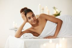 Beautiful african girl in towel smiling relaxing resting in spa salon. Young beautiful african girl in towel smiling relaxing resting in spa salon Royalty Free Stock Photography
