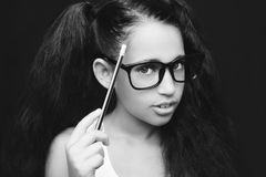 Beautiful African kid girl in glasses holding pencil in hand. A beautiful African kid girl in glasses holding pencil in hand Stock Photo