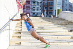 Beautiful african sport woman doing stretches, healthy concept. Stock Photos