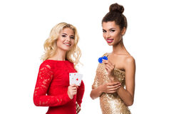 Beautiful african woman and Caucasian young woman with long light blonde hair in evening outfit. Holding playing cards stock photo