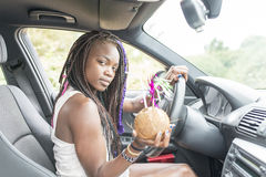Beautiful african woman with coconut cocktail in the car. Royalty Free Stock Image