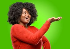 Beautiful african woman with curly hair. Beautiful african woman holding something in his empty hand Royalty Free Stock Photos
