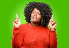 Beautiful african woman with curly hair isolated over green background Royalty Free Stock Images
