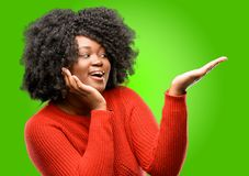 Beautiful african woman with curly hair isolated over green background. Beautiful african woman holding something in his empty hand Stock Images
