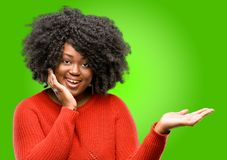 Beautiful african woman with curly hair isolated over green background. Beautiful african woman holding something in his empty hand Royalty Free Stock Images