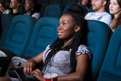 Beautiful African woman enjoying a movie Stock Photo