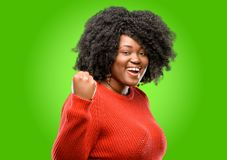 Beautiful african woman with curly hair isolated over green background Stock Photo