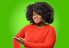 Beautiful african woman with curly hair. Beautiful african woman holding something in his empty hand Stock Images