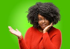 Beautiful african woman with curly hair isolated over green background. Beautiful african woman holding something in his empty hand Stock Photos