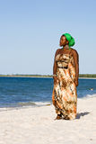 Beautiful african woman looking at the ocean. Beautiful african young woman looking thoughtfully at the ocean Royalty Free Stock Photos