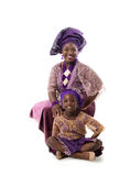 Beautiful African woman and lovely little girl in traditional dress.Isolated. Beautiful African women and lovely little girl sitting on floor in traditional Royalty Free Stock Images