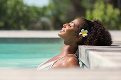 Beautiful african woman in pool relaxing royalty free stock photography